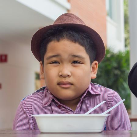 junky: Cute boy enjoy eating food Stock Photo