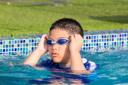 Cute little boy with his goggles on in swimming pool photo