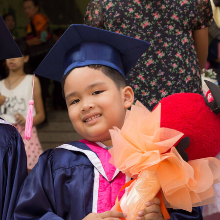 Asian kid in graduation gown and cap. photo