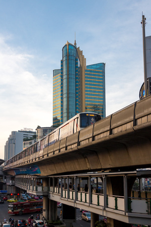 considerably: Bangkok, Thailand - October 4, 2014: BTS train rushes out of Asok station in Bangkok along Sukhumvit road. This elevated train system has helped considerably to reduce traffic congestion in the city, October 4, 2014 in Bangkok. Editorial