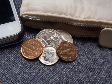 dime: US dollar coins placed outside the wallet with smartphone. Stock Photo