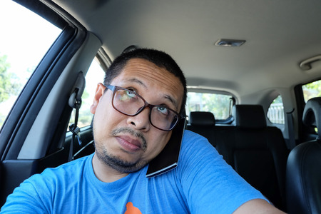 Asian man using phone while driving the car photo