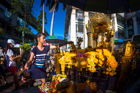 aisles: BANGKOK, THAILAND - JUNE 9: young girl pray respect the famous Erawan shrine at Ratchaprasong Junction Thailand on June 9, 2015.