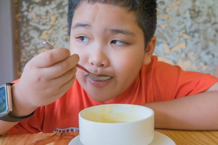 mushroom soup: Cute Asian boy eating mushroom soup.