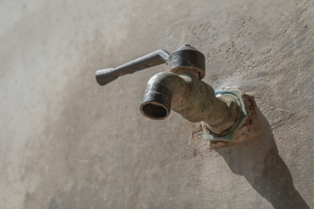 old faucet on concrete wall, save the water concept Stock Photo