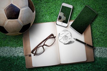 balon de futbol: balón de fútbol, ??cuaderno de dibujo, gafas, teléfonos inteligentes en el césped artificial verde Foto de archivo
