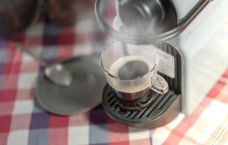 stimulating: machine serving espresso coffee in a glass cup