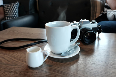 Cup of coffee with old film camera on wood table.