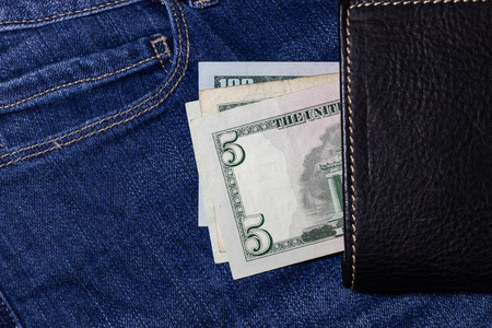 USA money, US DOLLAR, US Banknote inside black leather wallet on Jean Background.