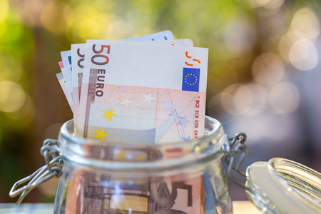 Euro banknotes in glass jar.