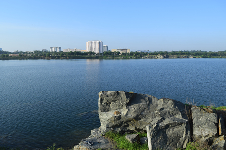 shrubs: rocky lake with some stones and grass in the bank near Ho Chi Minh city, vietnam