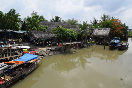 uncomplicated: traditional asian fishing boat in river and rural village, vietnam Editorial