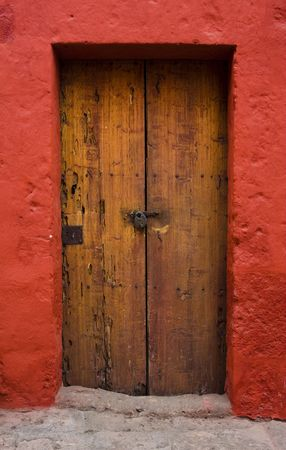 close up of ancient wood door and red wall photo