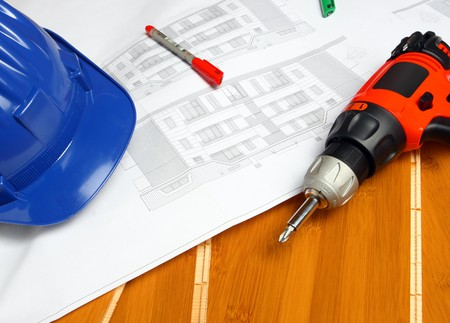 worker tool, blueprint, helmet and  drill on wood bamboo floor photo