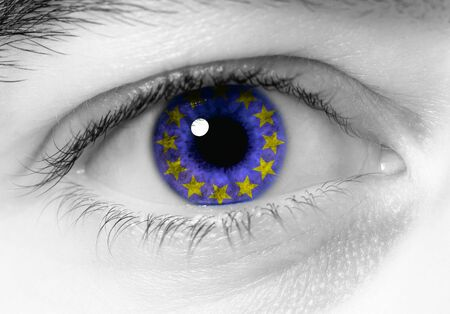 european community: black and white close up of eye with blue europe flag