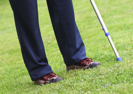 fine detail of man standing with crutches on lawn photo