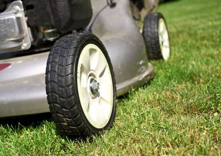 detail of classic Lawn Mower on green grass background photo