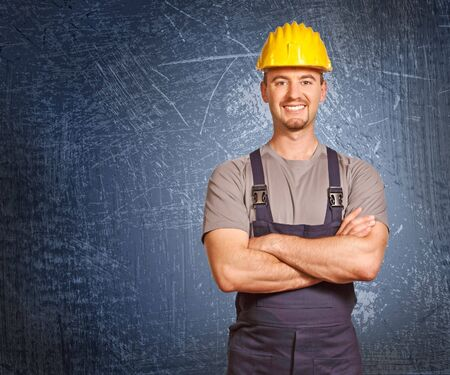 journeyman technician: positive pose of handyman and grunge background Stock Photo