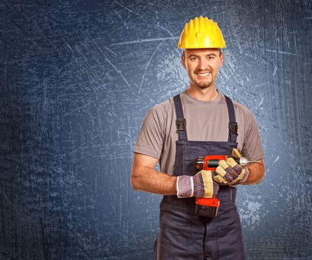 journeyman technician: portrait of young manual worker and blue grunge background