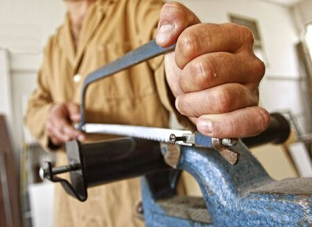 hand tool: detail of carpenter at work sawing metal object Stock Photo