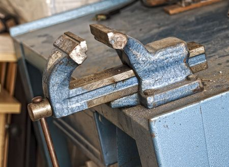 holdfast: fine detail of classic blue old banch vice on work place
