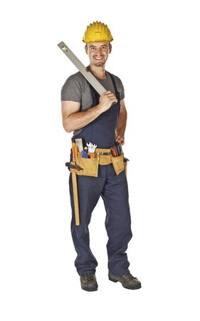 standing young caucasian handyman isolated on white with spirit level in his hand photo
