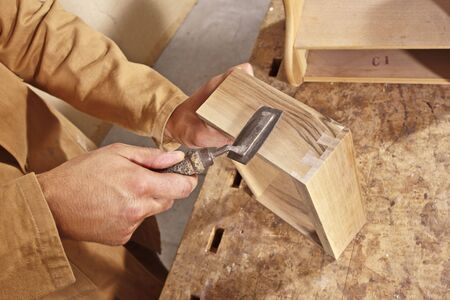 timbering: detail of caucasian carpenter at work with tool