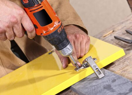 detail of caucasian carpenter at work with red tool photo