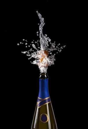 popping the cork: champagne bottle with shooting cork on black background