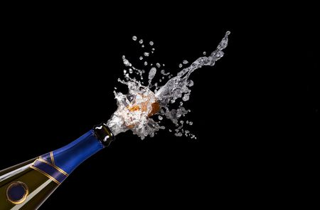 champagne bottle with shooting cork on black background
