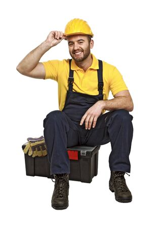journeyman technician: portrait of young caucasian handyman sit on his toolbox on white background