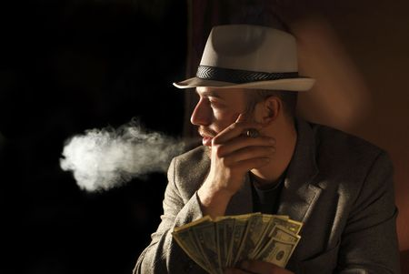 cigar smoking man: classic portrait of young gangster smoking and count dollars