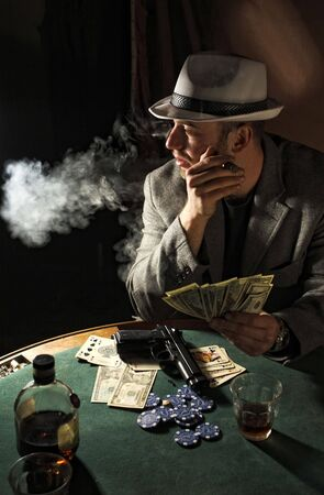 portrait of young gangster smoking and play poker