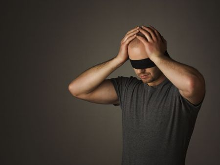 blindfold: portrait of young blindness man on dark background