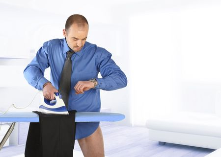 businessman hurry to ironing his trouser becose time to go work photo