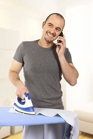 young man ironing his clothes and speat at mobile photo