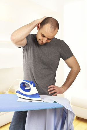 young man try to ironing his clothes without success Stock Photo - 6608656