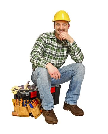 young handyman sit on his toolbox isolated on white Stock Photo - 6632286