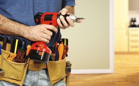 mantenimiento: detalles sobre el manual trabajador de manitas, toolsbelt y taladro rojo en sus manos  Foto de archivo
