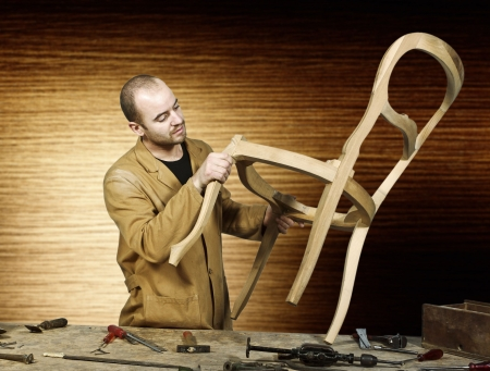 timbering: fine portrait of craftsman at work isolated and wood background