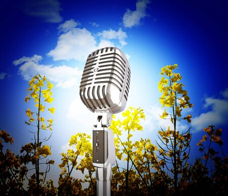 microphone, yellow flowers field  and blue sky background photo
