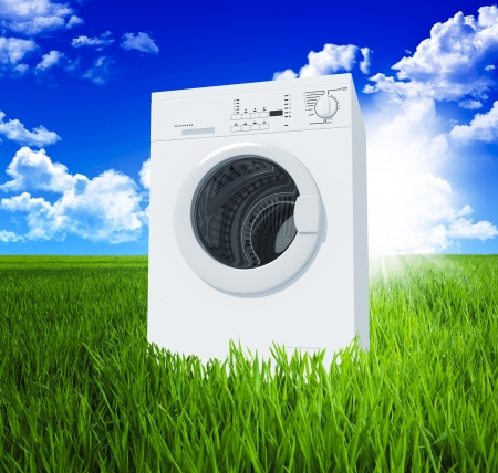 wet clothes: washing machine and green  field  with blue sky 3d background