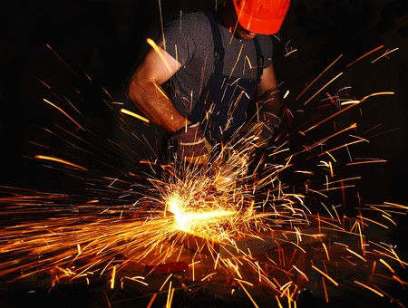 grinding: labor aty work with electric grinder, industrial background Stock Photo