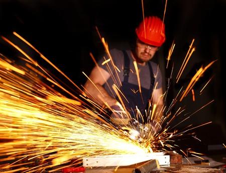 Handyman mit elektrischen Schleifer diensthabende, industrielle Hintergrund  Standard-Bild - 7231437