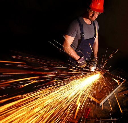 caucasian labor work with electric grinder on metal part photo