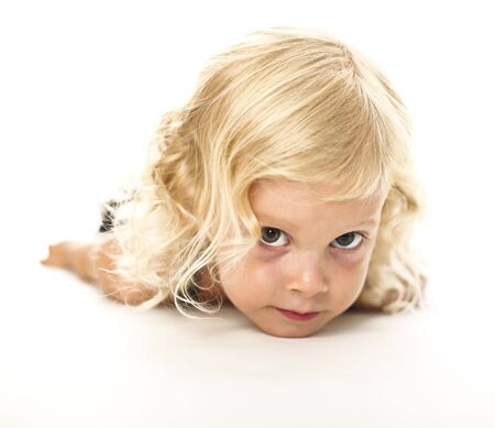 pretty blonde girl: funny portrait of blond adorable little lay down girl Stock Photo