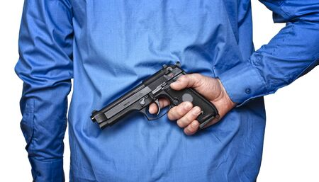 businessman hide pistol behind his back on white photo