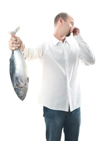 smell: hombre joven celebrar un pescado mal olor en su enfoque selectivo de mano  Foto de archivo
