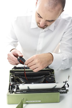 man try to fix vintage typewriter selective focus image Stock Photo - 7814367