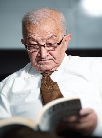 portrait of old man reading a book photo